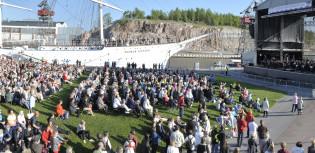 Konserttiyleisöä etualalla, vasemmalla esiintymislava ja taustalla Suomen joutsen