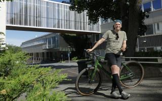 Shortseihin, t-paitaan ja lippikseen pukeutunut mieshenkilö seisoo ja nojaa polkupyörään. Ympärillä vaaleita rakennuksia ja vihreitä pensaita.